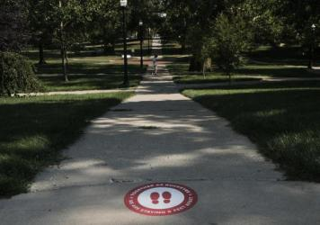 A sign on the ground at The Ohio State University reminds students to practice social distancing. The university has issued more than 200 interim suspensions to students linked to off-campus parties.