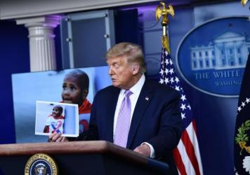 President Trump holds a photo of LeGend Taliferro, a boy killed in Kansas City, Mo., during a White House news conference.