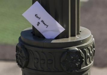 "A paper envelope written with the words ""Rent Money $"" is left tucked in a lighting pole in April in the Boyle Heights area of Los Angeles. Amid massive job losses due to COVID-19, California Gov. Gavin Newsom signed an extended eviction moratorium on Mo"