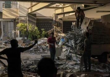 """Workers remove debris from a hospital that was heavily damaged in last month's explosion in Beirut. Lebanon's interim health minister, Hamad Hasan, told local media last month that the health system was """"on the brink"""" of being overwhelmed because of the"""