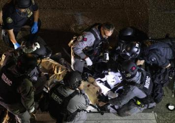 Emergency personnel treat Aaron Danielson in Portland, Ore., Aug. 29. The man suspected of killing Danielson, Michael Reinoehl, was killed by law enforcement agents as they attempted to arrest him Thursday night.