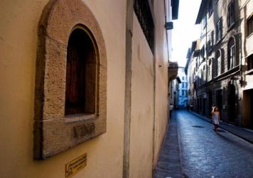 A girl walks past a <em>buchetta del vino</em>, a small window to serve wine, typical in Florence.