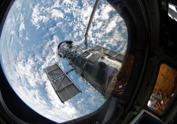 An STS-125 crew member onboard the Space Shuttle Atlantis snapped a still photo of the Hubble Space Telescope following grapple of the giant observatory by the shuttle.
