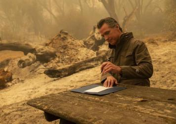 California Gov. Gavin Newsom signs Assembly Bill 2147 after he toured the North Complex Fire zone on Friday.  The bill allows inmates who have worked as firefighters to ask the court to dismiss their charges to make it easier for them to find a job once