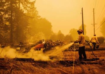 Oregon firefighters put out embers in Mill City, Ore., on Sept. 10, 2020, as they battle the Santiam Fire. As fires ravage the Pacific Northwest, fear and rumors have taken hold on social media.