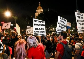 People protest the grand jury decision in the Breonna Taylor case in front of the Colorado state Capitol in Denver on Wednesday. As the protest was breaking up, a motorist drove through a small crowd of protesters who had yelled at the driver to turn aro