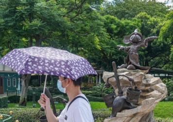A visitor wears a mask while walking by Mickey Mouse at Hong Kong Disneyland.