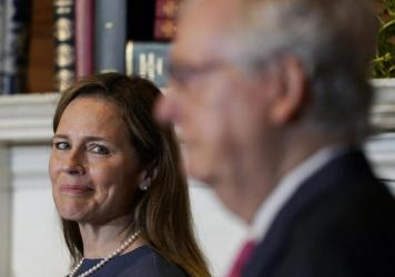 Supreme Court nominee Judge Amy Coney Barrett looks over to Senate Majority Leader Mitch McConnell of Kentucky on Capitol Hill Tuesday.
