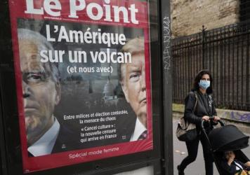 """The French weekly <em>Le Point</em> displays a photo of President Trump and Democratic presidential candidate Joe Biden under a headline reading """"America on a volcano (and us too)"""" in Paris, on Wednesday."""