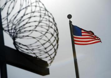A U.S. flag flies above a fence at the detention facility at the U.S. Naval Station at Guantánamo Bay, Cuba, on Dec. 10, 2008, in an image reviewed by the U.S. military.