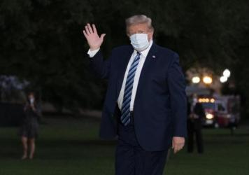 President Trump waves as he returns to the White House on Monday after leaving Walter Reed National Military Medical Center.