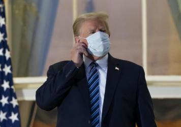 President Trump removes his mask upon returning to the White House on Monday after undergoing treatment for COVID-19 at Walter Reed National Military Medical Center in Bethesda, Md.