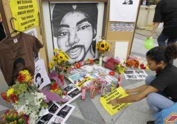 A woman leaves a sign at a street-side memorial to shooting victim Oscar Grant in Oakland, Calif., in 2010. A Northern California prosecutor announced Monday that she will reopen the investigation into the killing of Grant at a train station by a police