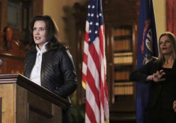Michigan Gov. Gretchen Whitmer addresses the state during a speech Thursday in Lansing. Thirteen members of two militia groups face criminal charges after allegedly plotting to kidnap Whitmer.