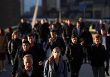 Commuters walk over London Bridge toward the city during the morning rush hour on Thursday. The city and other large areas are set to be under a high alert for the coronavirus.