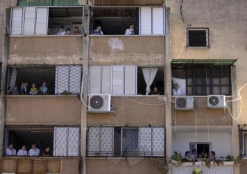 Ultra-Orthodox Jews watch a funeral for Rabbi Mordechai Leifer from their balconies in the port city of Ashdod, Israel, on Oct. 5. The rabbi, who had been the spiritual leader of a small ultra-Orthodox community founded a century ago in Pittsburgh, died