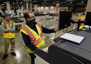John Hansberry with the Philadelphia City Commissioners Office runs a sorting machine at the city's mail-in ballot sorting and counting center on Oct. 26.