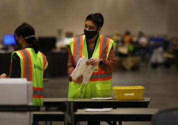 Election workers in Philadelphia count ballots on Tuesday. Pennsylvania is among several swing states that have yet to be called.