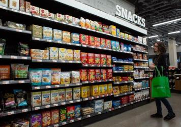 A pre-pandemic Seattle supermarket boasts row after row of prepackaged snacks. Even before the pandemic put extra stress on grocery workers, keeping shelves stocked with the variety Americans have come to expect took a hidden toll on producers, distribut