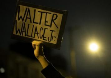 "A demonstrator holds a placard reading ""WALTER WALLACE JR."" during a protest near the location where Walter Wallace, Jr. was killed by two police officers on Oct, 27 in Philadelphia."