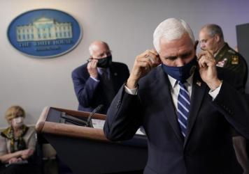 Vice President Pence adjusts his face mask during a news conference with the coronavirus task force at the White House on Thursday.