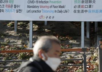 A man wearing a face mask walks past a banner showing precautions against the coronavirus in Seoul on Monday.