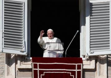 Pope Francis waves as he arrives for the Angelus noon prayer from the window of his studio overlooking St. Peter's Square, at the Vatican, Sunday.
