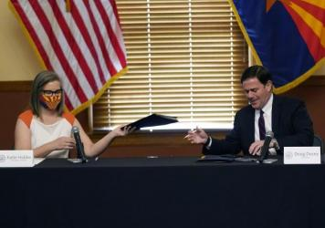 Arizona Secretary of State Katie Hobbs and Gov. Doug Ducey exchange election documents as they certify election results Monday at the Arizona Capitol in Phoenix.