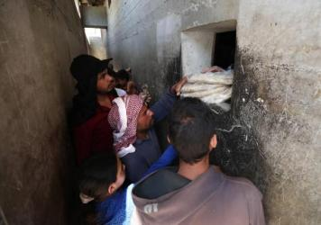 Syrians buy bread at a shop in the town of Binnish in the country's northwestern Idlib province in June. Nowadays, people say they're waiting up to six hours in line for a meager government bread ration.