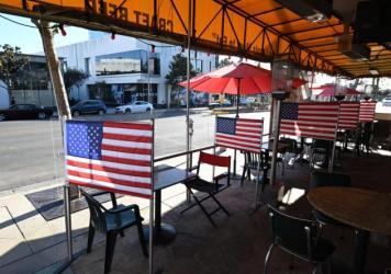 Empty patio tables are seen at a diner in West Hollywood, Calif. on Nov. 30, 2020, after Los Angeles County banned outdoor dining amid the pandemic. The struggles being experienced by restaurants and retailers are expected to have led to sharply slower j