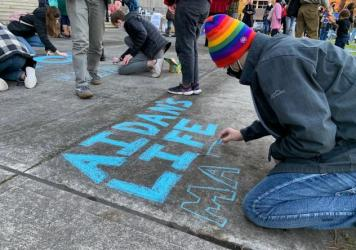 Toren McKnight of Central Point draws on the cement at the vigil for Aidan Ellison outside the Jackson County Courthouse in Medford, Ore., on Dec. 3.