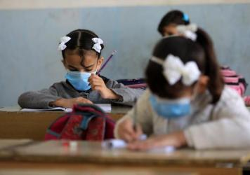 Students wear masks at a school in Baghdad.