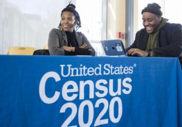 Chris Worrell jokes with Teresa Jefferson while applying for a 2020 census job in Boston in February before the COVID-19 pandemic. Based on government records, the Census Bureau estimates the U.S. population has grown by as much as 8.7% since 2010.