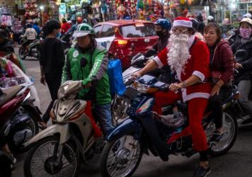 A man in a Santa Claus costume rides a motorbike in the Old Quarter on Dec. 24, 2020, in Hanoi, Vietnam.