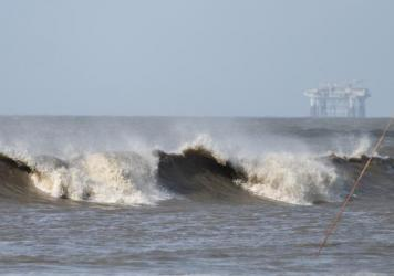 Hurricane Laura sends large waves crashing on a beach in Cameron, La., on Aug. 26 as an offshore oil rig appears in the distance. The most active hurricane season on record was just one of many challenges facing the oil industry this year — aside from