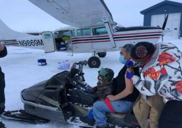 Sarah Lind, a nurse with Yukon-Kuskokwim Health Corp., Southwest Alaska's tribal health care provider, vaccinates James Evan in December, 2020. They're standing on the tarmac in the village of Napakiak, where Evan works for YKHC at the clinic.