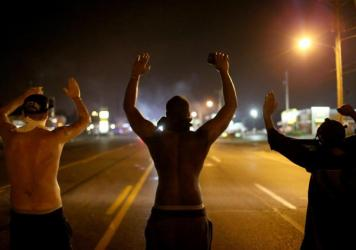 "Demonstrators raise their arms and chant ""Hands up, don't shoot"" on Aug. 17, 2014, as they protest the shooting death of Michael Brown in Ferguson, Mo."