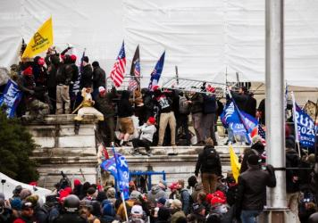 Pro-Trump extremists climb the walls of the U.S. Capitol on Jan. 6. The pro-Trump mob broke windows of the Capitol and clashed with police officers. Now there's debate about whether federal charges of seditious conspiracy should be used against some of t