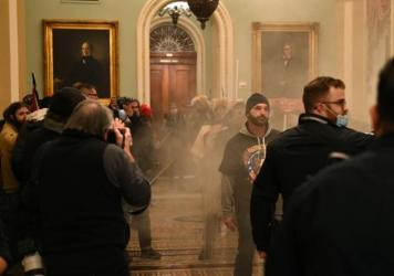 Supporters of U.S. President Donald Trump storm the U.S. Capitol as smoke fills the corridor on January 6, 2021, in Washington, DC.