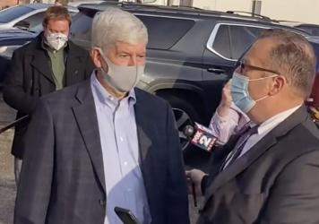 In this image taken from video, former Michigan Gov. Rick Snyder, left, with his lawyer, Brian Lennon, leave Genesee County Court in Flint, Mich., after a initial court appearance via Zoom on two misdemeanor counts of willful neglect of duty in connectio