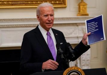 President Joe Biden holds a booklet as he speaks about the coronavirus in the State Dining Room of the White House, Thursday.