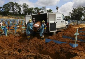 Cemetery workers carry the remains of 89-year-old Abilio Ribeiro, who died of the new coronavirus, for burial at the Nossa Senhora Aparecida cemetery in Manaus, Amazonas state, Brazil, on Jan. 6. The day before, Manaus declared a 180-day state of emergen