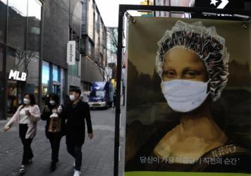 South Korea's KF94 mask does a good job concealing the <em>Mona Lisa</em>'s smile — but how effective is it at preventing coronavirus spread? Here, masked pedestrians stroll through a shopping district in Seoul.