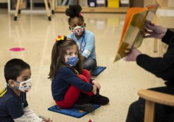 Prekindergarten students listen as their teacher reads a story this month at Dawes Elementary School in Chicago.
