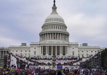 Rioters storm the Capitol on Jan. 6. Three individuals associated with an extremist group were indicted Wednesday on charges that include conspiracy and obstructing an official proceeding.