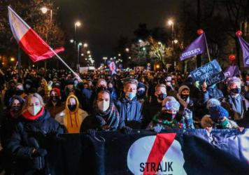 Protesters against new restrictions on abortion walk toward the Law and Justice Party headquarters on Wednesday night in Warsaw. A Constitutional Court ruling in October determined that abortions are only legal in cases of rape and incest, and when the m