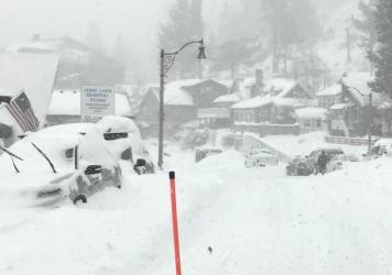 In this photo provided by Caltrans District 9, heavy snowfall blankets cars at June Lake, in Mono County, Calif., on Wednesday. The same storm that brought snow and heavy rain to the state is moving through the Midwest, with 5 to 9 inches of snowfall pre