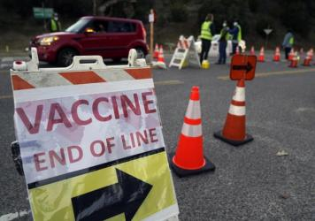 Drivers with an appointment enter a COVID-19 vaccination site set up in the parking lot of Dodger Stadium in Los Angeles on Saturday. One of the largest vaccination sites in the country, it was temporarily shut down Saturday afternoon because of proteste