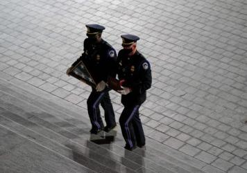 An honor guard carries an urn with the cremated remains of  Capitol Police officer Brian Sicknick and a folded American flag up the steps of the U.S. Capitol on Tuesday.