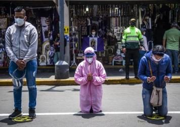 Worshippers pray in the streets of Lima. A government lockdown has shutdown churches as well as businesses to try to stop the spread of the virus.